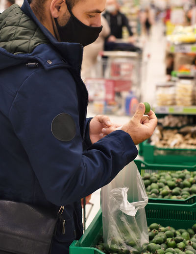 Midsection of man wearing mask standing at supermarket