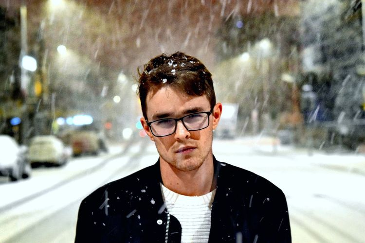 Close-up portrait handsome young man standing on road during snowfall
