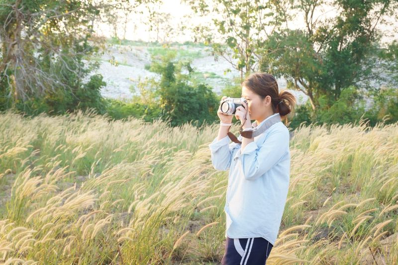 Photography Themes Camera - Photographic Equipment Photographing Plant Holding Technology Activity Women Field Nature Grass Land Lifestyles Casual Clothing Three Quarter Length Togetherness