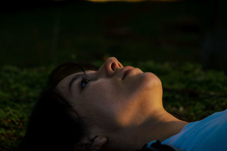 Close-up of young woman lying in park
