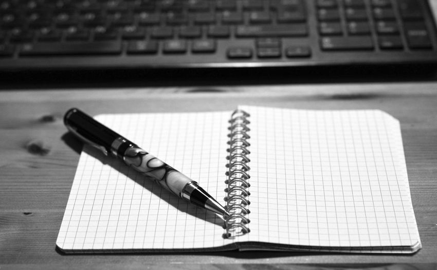 High angle view of pen over notepad on table