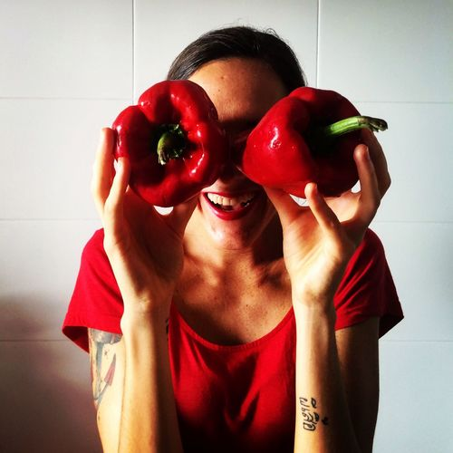 Smiling woman holding red bell pepper