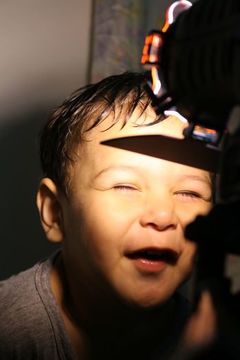 Close-up of boy with eyes closed in front of illuminated light at home