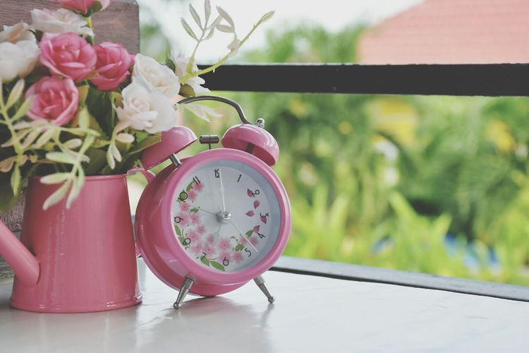 Close-up of pink alarm clock and flower vase on table at home
