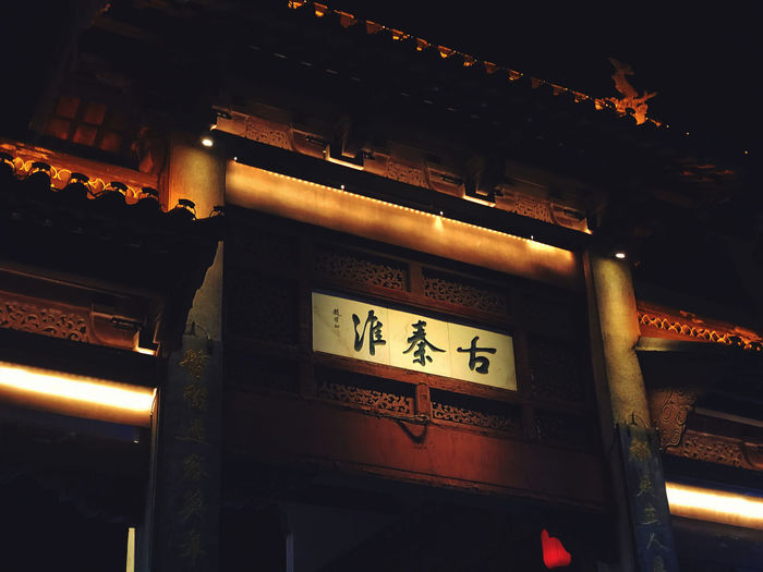 Low angle view of illuminated sign at temple
