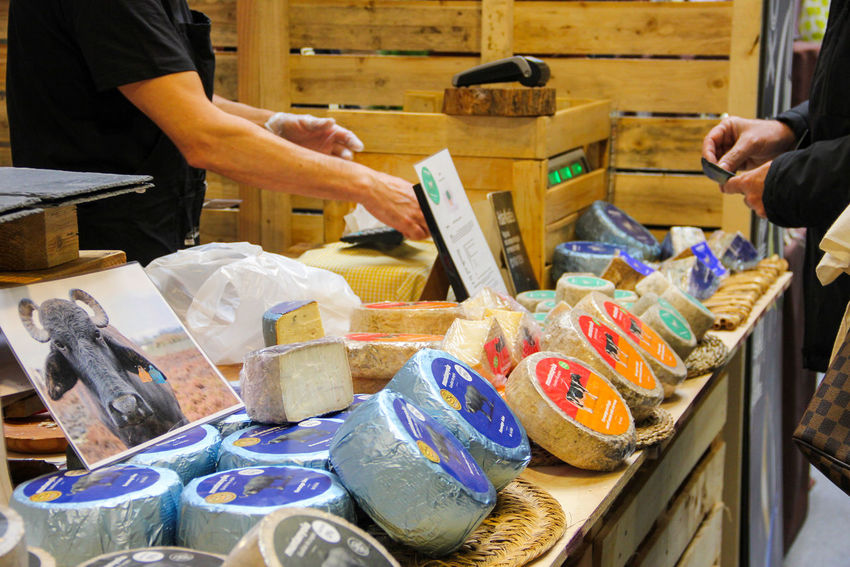 eople buy in a small bench cheese, which lies in the range. Shopping Arrangement Cash Register Cheese Close-up Counter Day Holding Human Hand Indoors  Midsection One Person People Purchase Purchases Real People Retail  Shopping Time Showcase Trade Business Stories