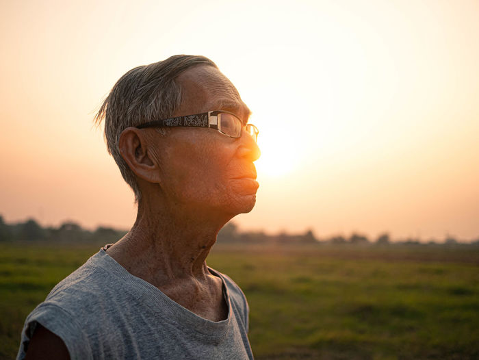 Senior man looking away while standing against sky during sunset