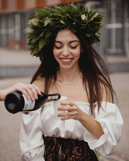 Young woman holding wine standing outdoors