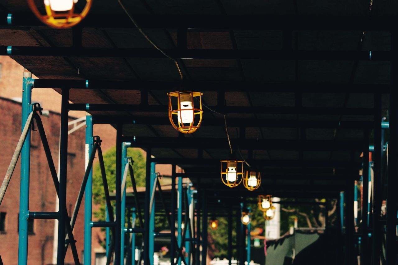 Low Angle View Of Illuminated Lighting Equipment Hanging In Covered Walkway