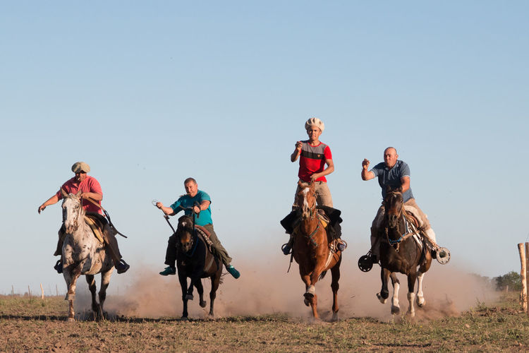 People riding horses on field against clear sky