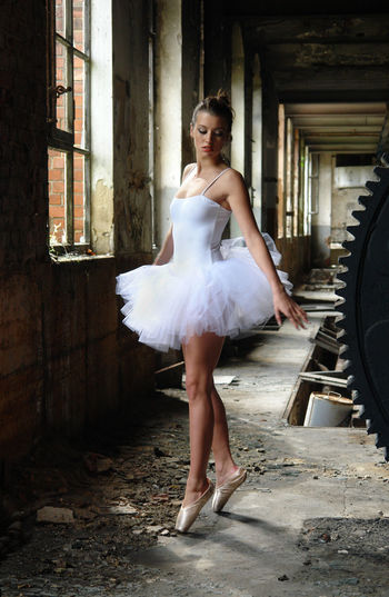 Full Length Of Ballerina Dancing In Abandoned Building