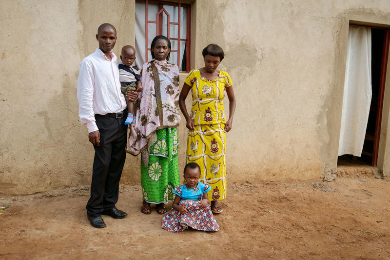 rural family at the front door of the house Casual Clothing Family Grandma Kigali Lifestyles Mid Adult Men Person Portrait Rural Smiling Togetherness Vilage