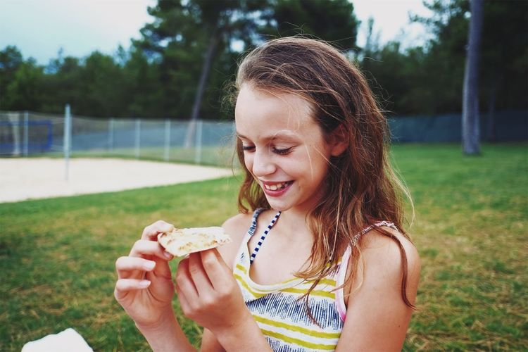 Close-up of girl eating food in park