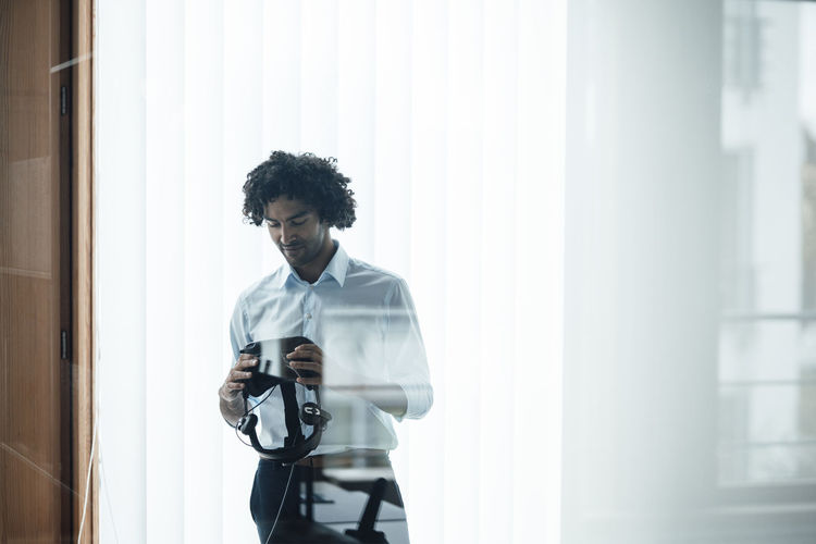 Young man photographing through window