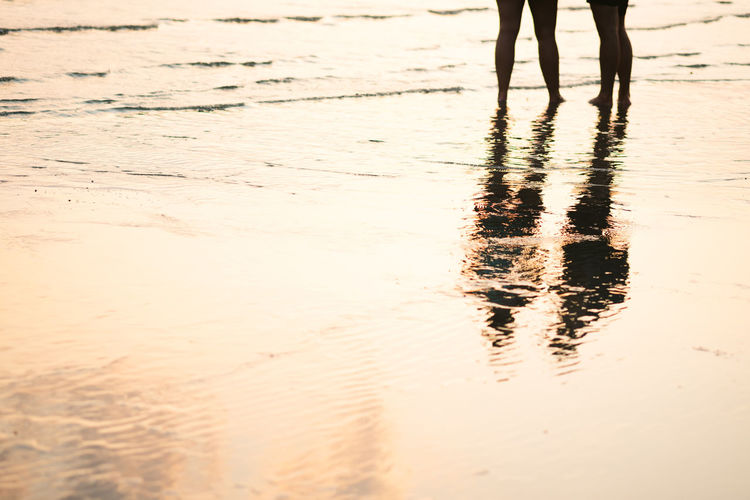 Silhouette of couple walking and talking on the beach with drop shadow reflected on calm sea water surface in evening sunset. Holiday vacation, relax and chilling on beach in summer used for background. Low Section Body Part Human Leg Reflection Real People Human Body Part Standing Walking Water Lifestyles Land Nature Beach Leisure Activity Wet Sand Outdoors Human Foot Reflections In The Water Couple Sea Sunset Romantic Love Silhouette