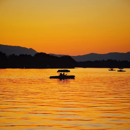 Sunset Mountain Transportation Lake Water Nature Outdoors Floating On Water Nautical Vessel Travel Destinations Landscape Sailing Beauty In Nature Warm Glow Yellow Summer Travel Hangzhou,China Light And Shadow Vacations West Lake, Hangzhou Lake View China View Tranquility Beauty In Nature