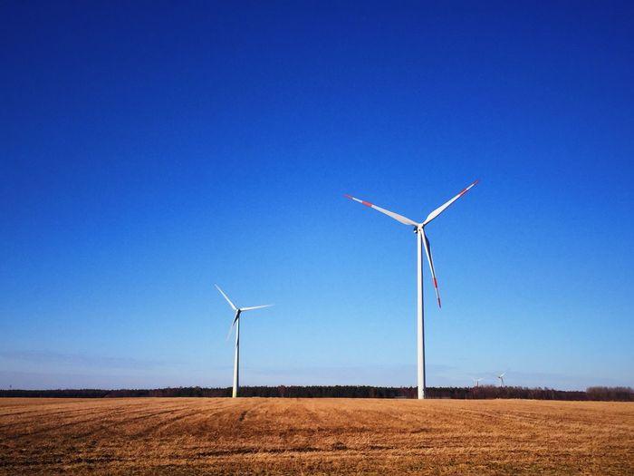 Windmill on field against clear blue sky