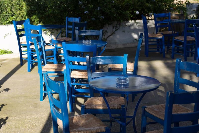 Kafeneion Chair Table Outdoor Cafe Absence Empty Outdoors Sidewalk Cafe No People Day Blue Sunlight Wood - Material Seat Place Setting Cafe Group Of Objects Furniture
