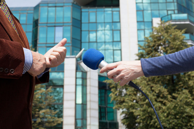 Journalist interviewing businessperson, corporate building in background Comment; Interview Journalist Press Broadcasting Building Businessman Businessperson Communication Corporate Hand Holding Information Journalism Media Microphone News Person Politician Question Report Reporter Suit; Unrecognizable Person