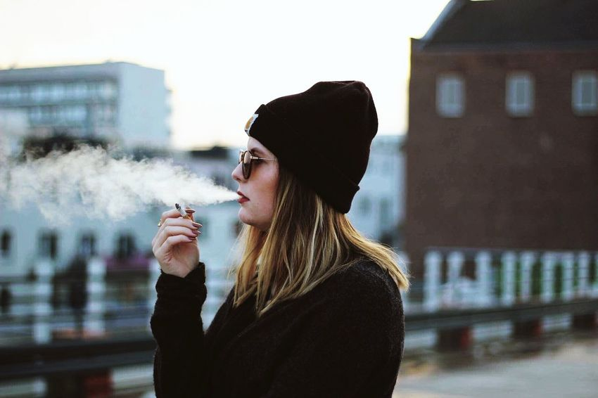 Smoking - Activity Cigarette  Smoking Issues Addiction Bad Habit Cigarette  Smoke City Outdoors One Young Woman Only Beautiful Woman Blond Hair Young Adult One Person Warm Clothing Smoke - Physical Structure One Woman Only Adults Only Only Women Winter Women City Young Women People Adult