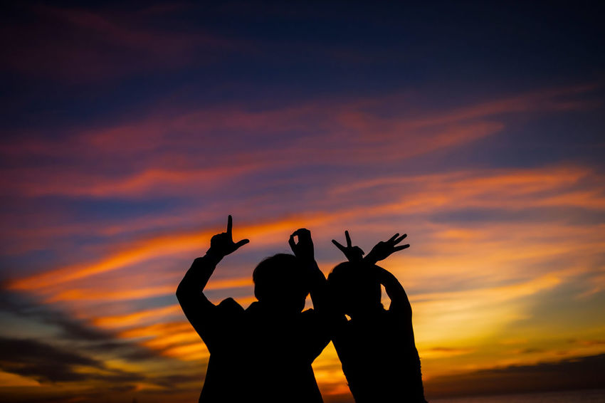 Arms Raised Beauty In Nature Cloud - Sky Gesturing Horn Sign Human Hand Leisure Activity Lifestyles Men Nature One Person Orange Color Outdoors Peace Sign - Gesture People Real People Scenics Silhouette Sky Sunset