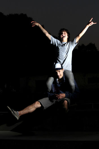 Man carrying friend on shoulders at night