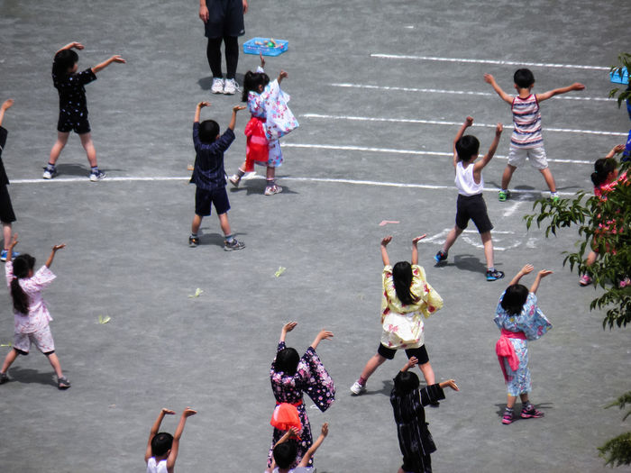 High Angle View Of Children Dancing With Arms Raised On Playground