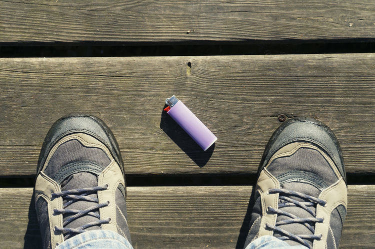 lighter on boardwalk Above View Boards Boardwalk Boots Downward View Fallen Floor Footwear Found High Angle View Hiker Hiking Lighter Object Outdoors People Planks Shoes Standing Wood