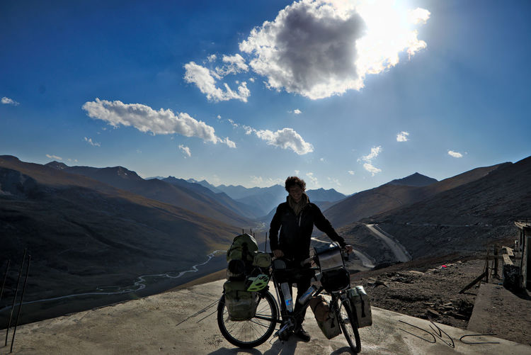 Man riding bicycle on mountain against sky