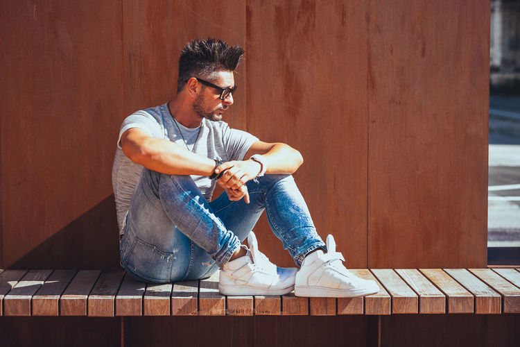 One Person Casual Clothing Sitting Full Length Real People Young Men Young Adult Wood - Material Lifestyles Leisure Activity Looking Glasses Looking Away Day Relaxation Fashion Front View Men Jeans Contemplation