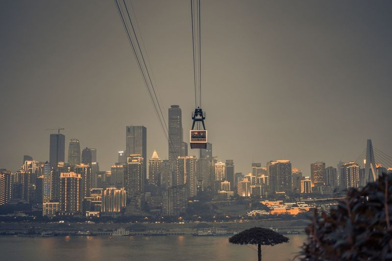 Overhead Cable Car Against Illuminated Cityscape At Night