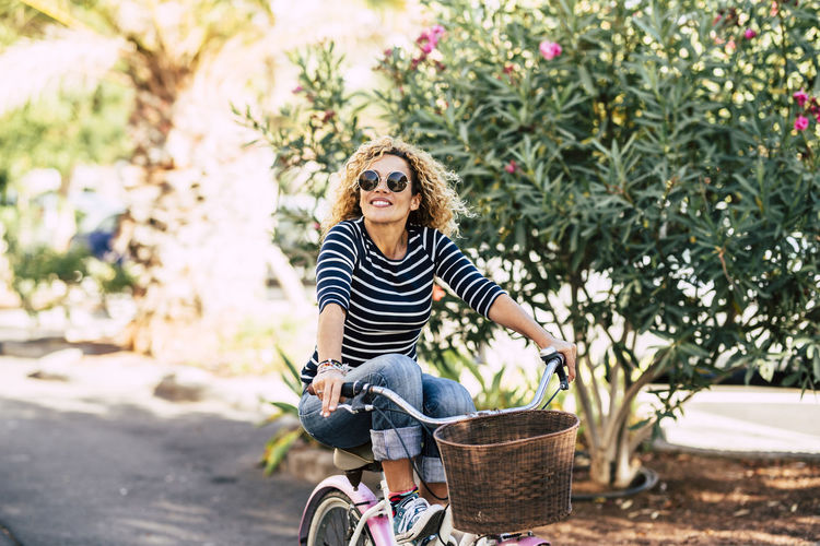 Smiling young woman riding bicycle against tree