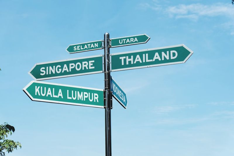 Kuala Lumpur Thailand Singapore Travel Destinations Travel Wheretogo Communication Sign Text Western Script Sky Guidance Road Sign Directional Sign Arrow Symbol Information Sign Road Direction
