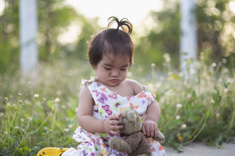 Cute girl with toy on plants