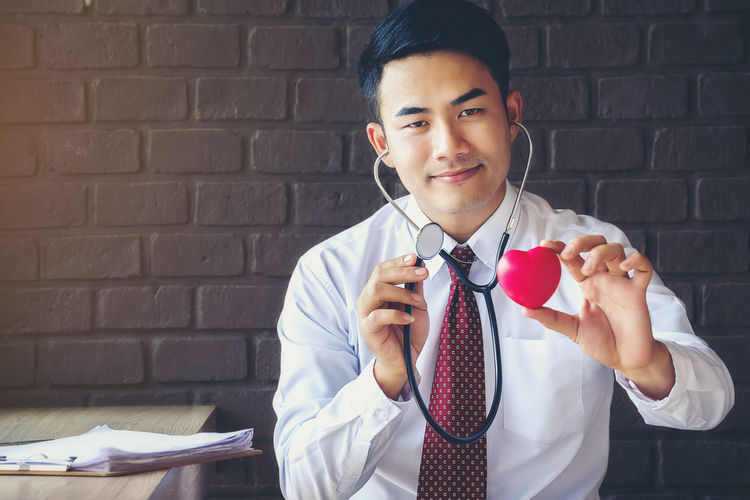 Portrait of smiling doctor holding model heart and stethoscope
