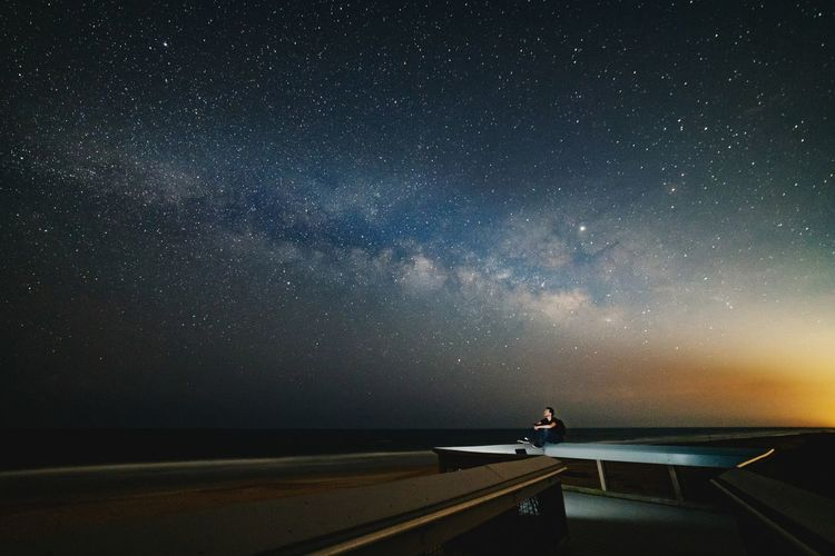 Man sitting on retaining wall against star field at night