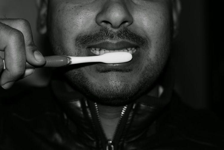 Cropped image of man brushing teeth