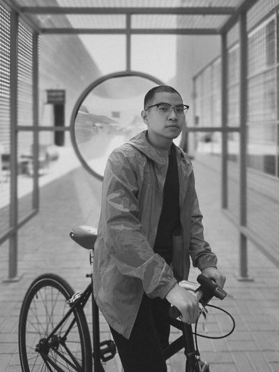 Portrait of young man with bicycle outdoors