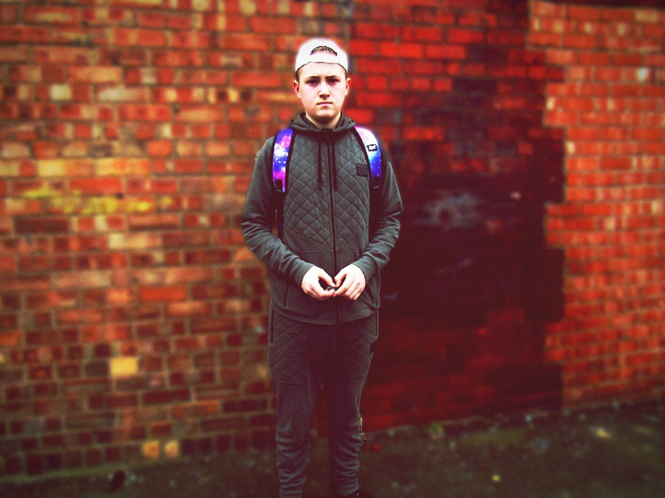 young adult, looking at camera, young men, portrait, one young man only, only men, standing, brick wall, attitude, one person, one man only, adults only, confidence, men, hipster - person, city, adult, people, outdoors, real people, day