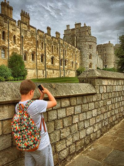 Boy With Smart Phone Photographing Windsor Castle Against Cloudy Sky