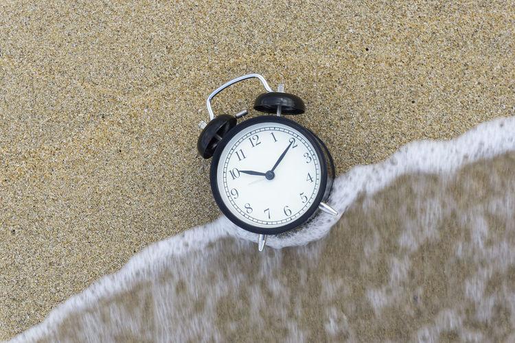 High angle view of alarm clock at sea shore