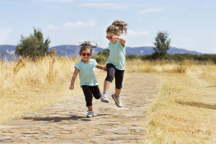 Happy Sisters Jumping On Footpath