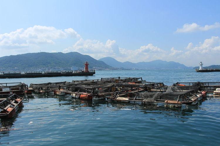 Fish farm at sea against cloudy sky