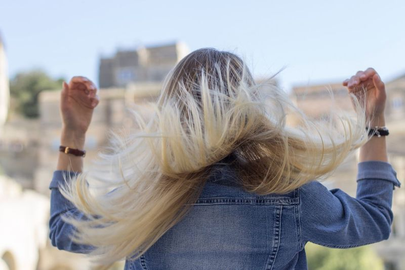 Rear view of woman tossing hair against buildings