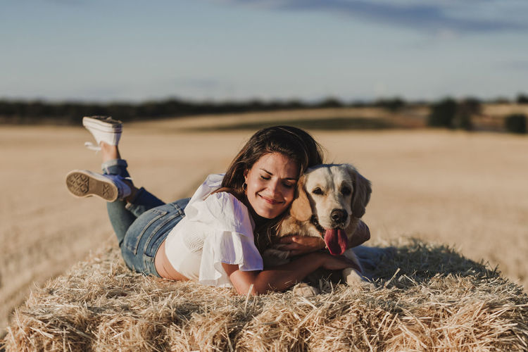 Happy mid adult woman with dog lying on hay at agricultural field