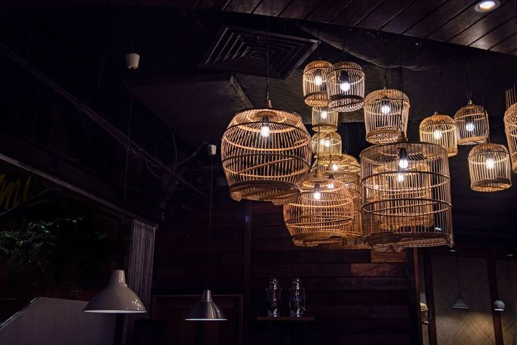 Low angle view of illuminated pendant lights hanging at restaurant