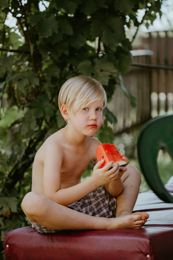 Portrait of shirtless boy holding food sitting outdoors