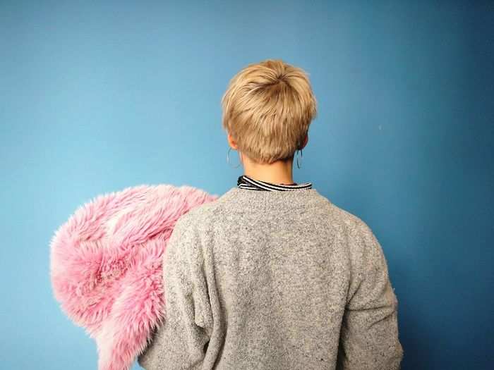 Rear view of a woman against blue background