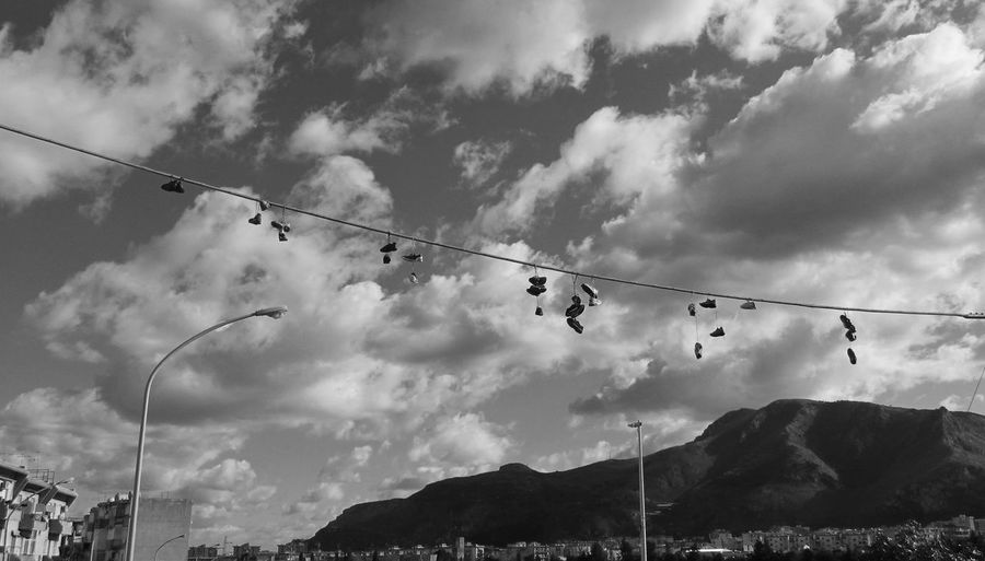 Low angle view of shoes hanging from power line