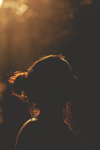 Close-up portrait of silhouette woman with illuminated lights at night